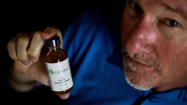 Georgia State Rep. Allen Peake displays a bottle of cannabis oil in his office in Macon, Ga. (Photo David Goldman / AP)